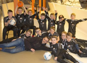 Foto: SKS. Die Nachwuchskicker der Spielgemeinschaft Hachen-Langscheid/Enkhausen bedanken sich bei einem Besuch im Unternehmen SKS für die gesponserten T-Shirts
